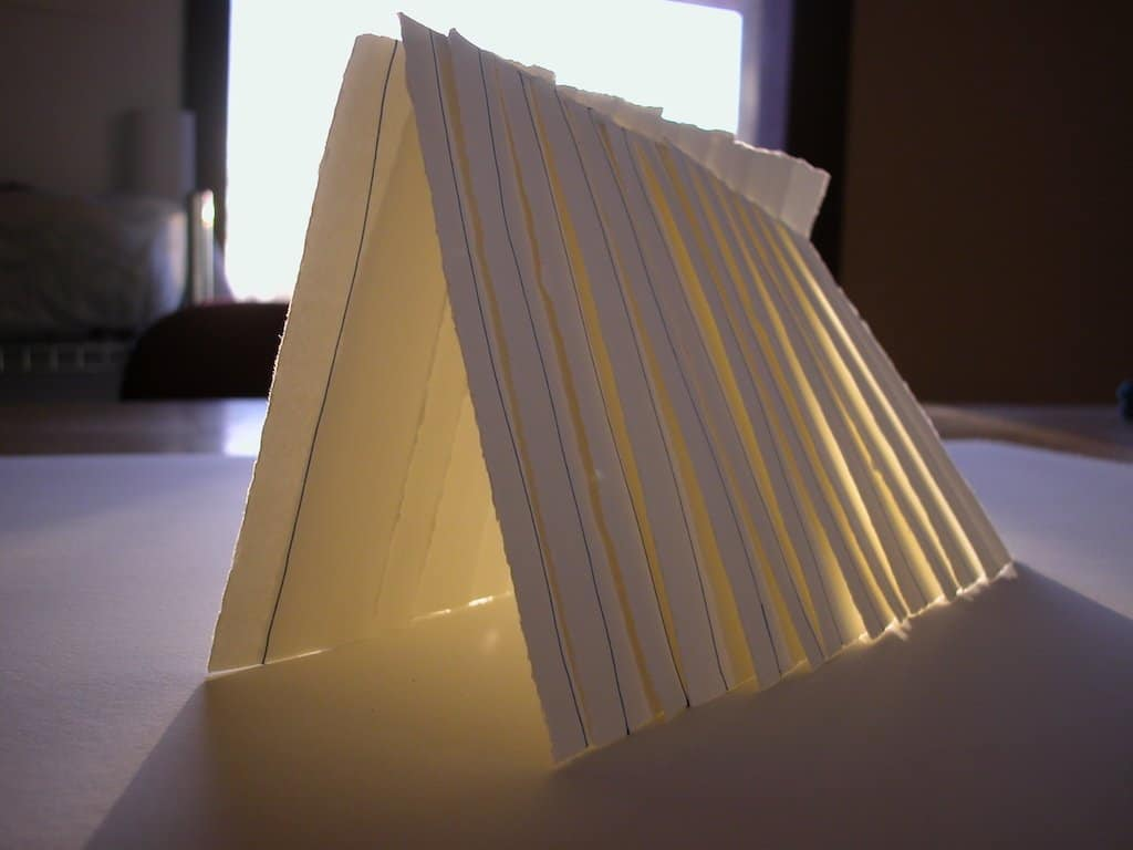 White paper 'cards' with blue lines drawn on them, propped up against each other, in the sunlight.