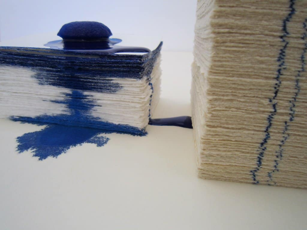 Blue ink melting down a stack of fine art paper.