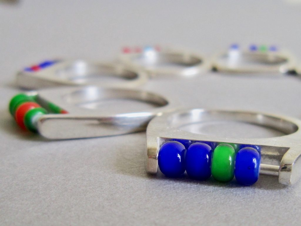 Colourful glass beads on rings. Blue and green.