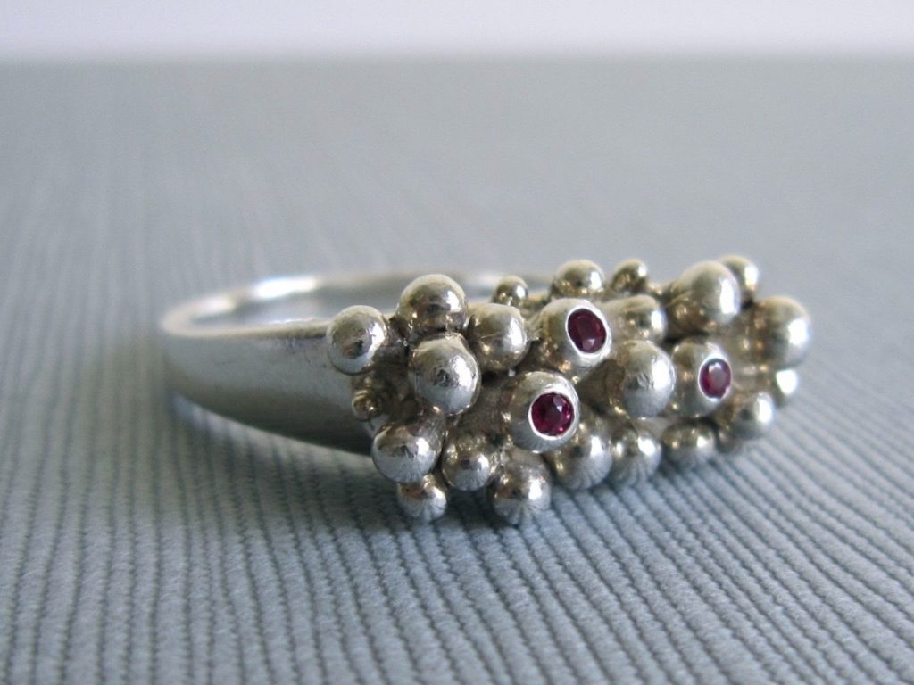 Close up of a silver ring with many bumps on the to top surface. Three red rubies are set in the tops of three of the bumps.