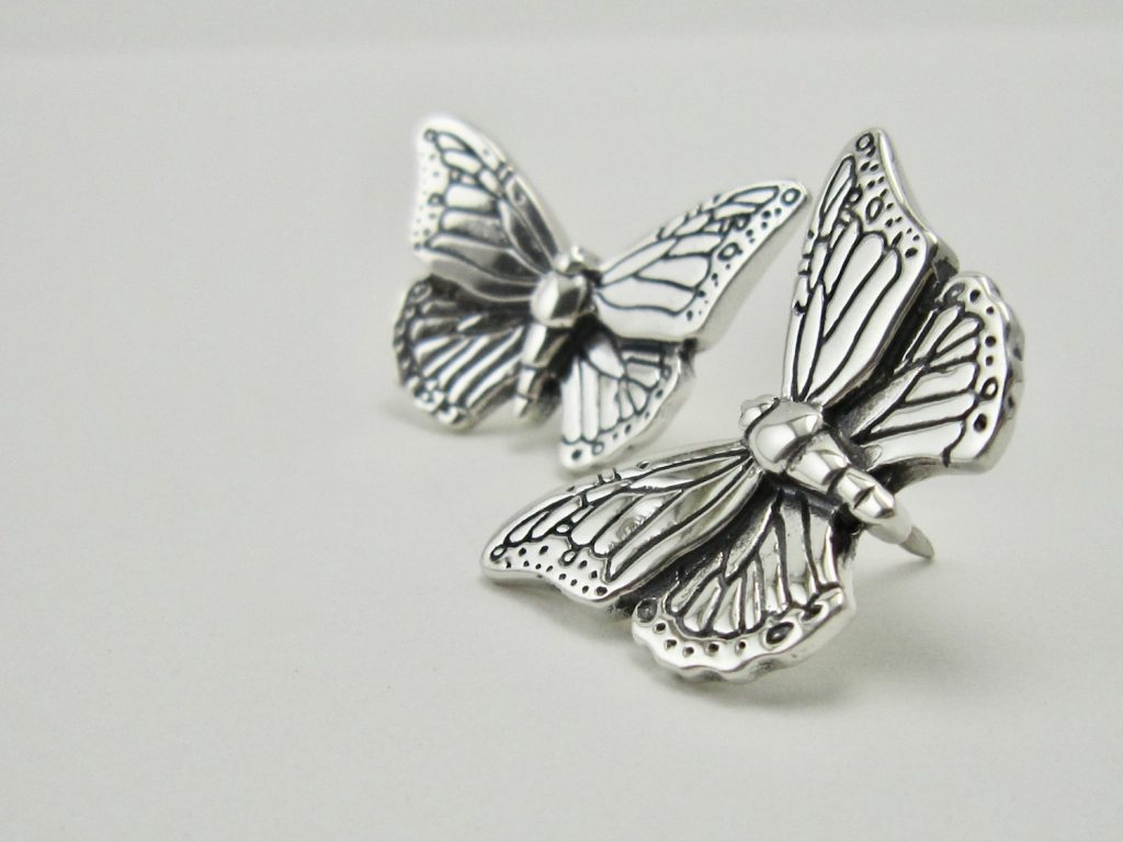 Two silver monarch butterfly pins.