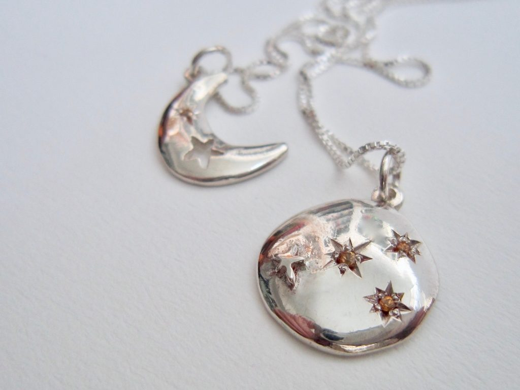 Two silver pendants: Crescent and full moon, with stars.