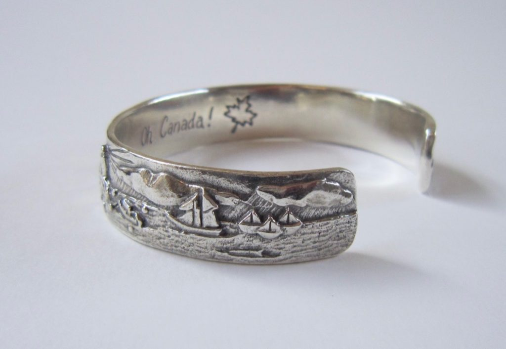 Close up of a silver cuff bracelet. Sailboats and 'Oh Canada' with a maple leaf can be seen on the inside surface.